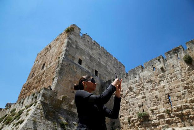 Sonam Kapoor takes a photograph during her visit to Jerusalem's Old City.