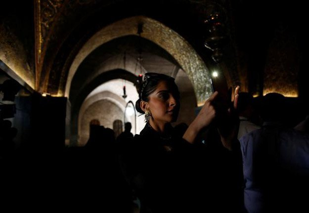 Sonam Kapoor takes a photograph during her visit to the Church of the Holy Sepulchre in Jerusalem's Old City